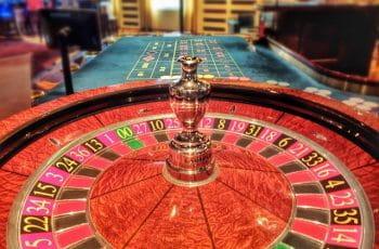 Nærbillede af roulettehjul og i baggrunden ses roulettebordet.