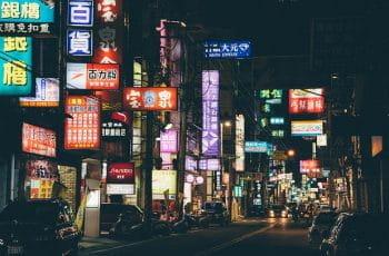 Udsnit af en gade i Kina. Det er aften og skiltene lyser i mørket.