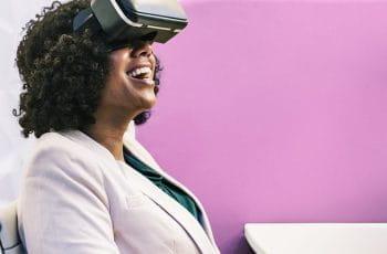 En kvinde med VR-briller set fra siden. Hun smiler.