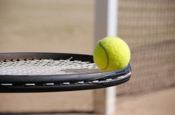 Tennisketcher med bold på ligger på stregen til banen.