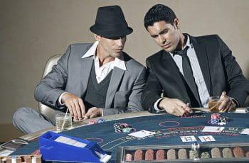 To spillere sidder ved et blackjackbord.