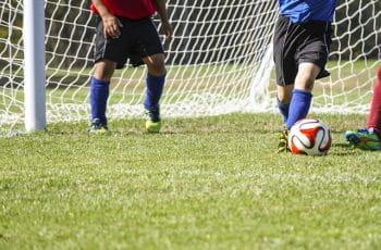 Der spilles fodbold foran et mål. Kun benene og bolden vises.