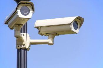 To overvågningskameraer hænger i en lygtepæl.