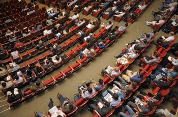 En masse mennesker sidder i et stort konferencerum.