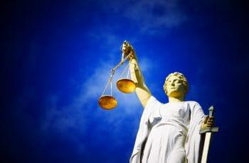 Retfærdighedens gudinde, Justitia, står med vægten i hånden.